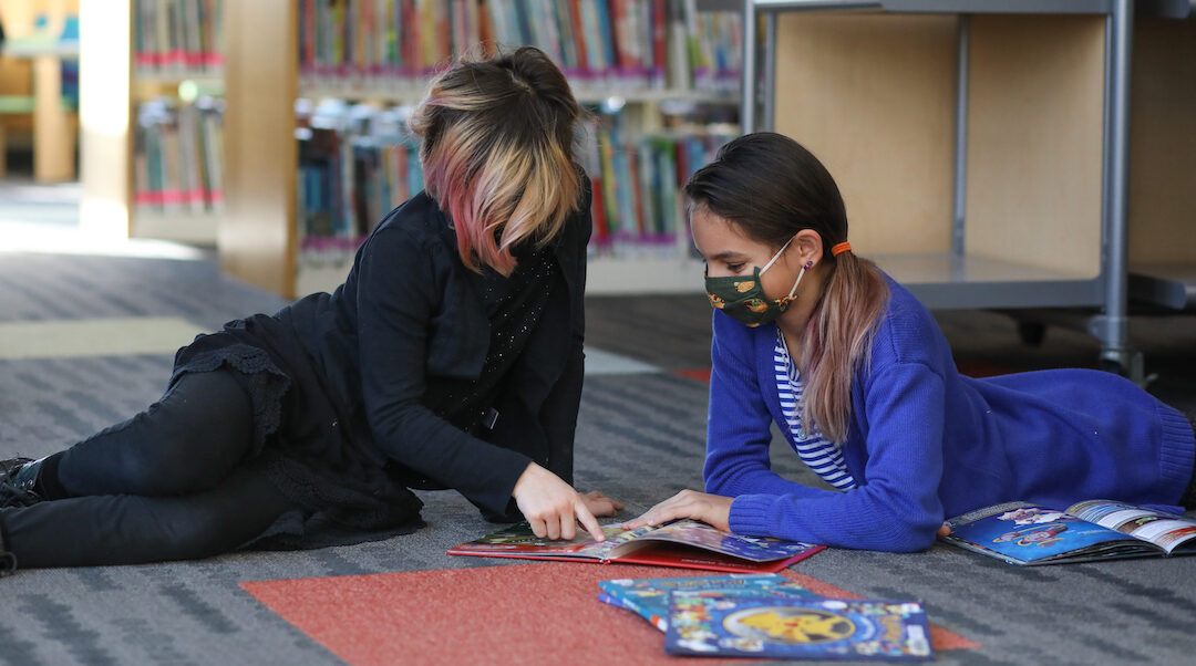 Preteen girls reading in library