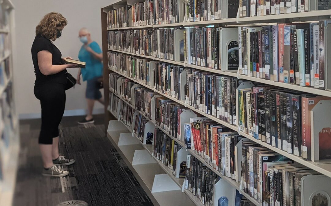 Woman selecting book in library