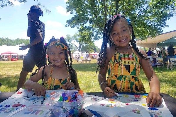 Girls doing We Read activities at Juneteenth festival